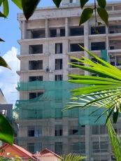 Cet homme travaille presque en haut d'un immeuble en construction, sans rien pour le retenir en cas de chute. Phnom Penh, Cambodge.