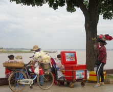 Des vendeuses itinérantes prennent une pause le long du Tonlé Sap avant de débuter leur soirée. Celle à bicyclette vend des noix, une autre vend des rafraîchissements et celle qui a un panier sur la tête vend des barrettes pour les cheveux. Phnom Penh, Cambodge.