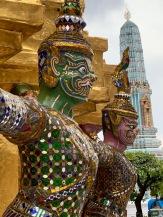 Une rangée de ces créatures mythiques maintient un des étages d'un stupa doré. Plus loin, un stupa recouvert de céramique. Site du Wat Phra Kaew et du Grand Palais. Bangkok, Thaïlande.