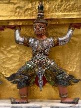 Une rangée de ces personnages semble maintenir les étages supérieurs d'un stupa doré. Wat Phra Kaew, Bangkok, Thaïlande.