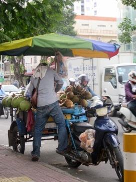 Un commerce itinérant: ce jeune homme vend des cocos qu'il prépare sur demande. Tout est frais. Phnom Penh, Cambodge.