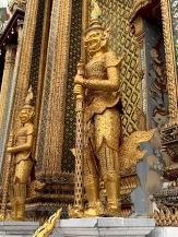 Des personnages mythiques montent la garde devant un édifice richement décoré, sur le site du Wat Phra Kaew et du Grand Palais. Bangkok, Thaïlande.