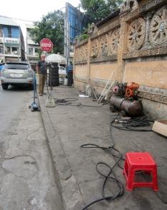 Si les pneus de votre moto manquent d'air ou que ceux de votre voiture doivent être changés, il est possible d'obtenir les services d'un garagiste sur le trottoir... Phnom Penh, Cambodge.