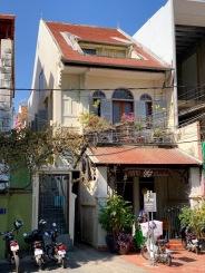 Une petite maison prise entre deux édifices. Le toit aurait besoin d'être rénové, mais elle est mignonne comme tout! Phnom Penh, Cambodge.