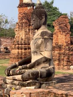 Un grand Bouddha de pierre nous accueille à l'entrée du Wat Maha That, Ayutthaya, Thaïlande.