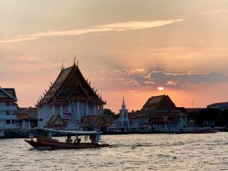 Le soleil se couche sur l'un des temples longé par le Chao Praya, Bangkok, Thaïlande.