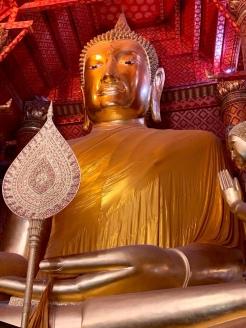 Un très grand bouddha doré nous accueille à l'entrée du temple. Il est magnifique et très imposant. Entouré de plus petits bouddhas, il a des fleurs à ses pieds, les murs et les plafonds sont entièrement recouverts de dorures. Wat Phanan Choeng Worawihan, Ayutthaya, Thaïlande.