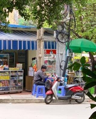 Un petit dépanneur au coin de la rue, en face de l'hôtel Anise, où nous achetons notre eau. Le matin, un moine vient y faire la prière et recueillir les offrandes. Des petits repas y sont servi, cuisinés tout près sur le trottoir. Il y a toujours de l'action, peu importe l'heure de la journée. Phnom Penh, Cambodge.
