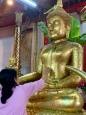 Une femme pose une feuille d'or sur un bouddha. Wat Phanan Choeng Worawihan, Ayutthaya, Thaïlande.
