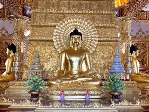 Quatre bouddhas dorés permettent de se recueillir depuis quatre positions différentes dans le temple. Devant chacun des bouddhas, des moines sont disponibles pour la prière. Wat Phra That Nong Bua, Ubon Ratchathani, Isan, Thaïlande.