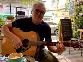Mon amoureux a trouvé une guitare au Garden Café et avec la permission du propriétaire, il profite de l'occasion pour jouer quelques mélodies. Khon Kaen, Isan, Thaïlande.