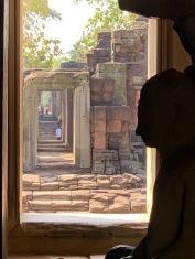 À partir du couloir central du Prasat Hin Phimai, une statue de Bouddha, protégé par les 7 têtes de Naga, se profile sur les vieilles pierres baignées de soleil, Phimai, Thaïlande.