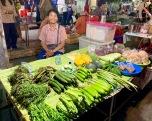 Une marchande offre ses légumes frais au marché de nuit de Nang Rong. Isan, Thaïlande.